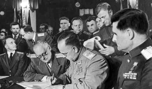 слева на право, Вышинский, привезший договор о капитуляции, и Жуков, подписывающий документ