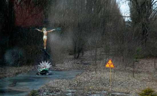 Распятие и знак радиации встречают на входе в Припять, но дождик и туман складываются в лицо призрака.